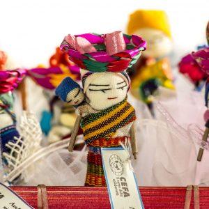 Bomboniera solidale composta da bambolina scacciapensieri del Guatemala colorata e artigianale con tulle porta-confetti e piccola pergamena che spiega il progetto sostenuto