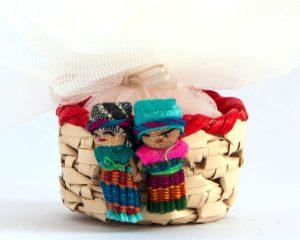 Bomboniera solidale composta da piccolo cestino in vimini con due piccolissime bamboline scacciapensieri. Dal cestino sbuca fuori un tulle rosa porta-confetti