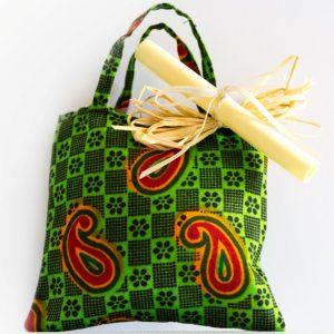 Bomboniera solidale composta da sacchettino porta-confetti realizzato artigianalmente con stoffa africana colorata, fantasia verde e rossa. Attaccatto con raffia al manico della borsina c'è una piccola pergamena arrotolata che spiega il progetto solidale